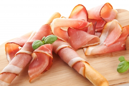 Luxurious prosciutto ham with grissini bread sticks and fresh basil on wooden cutting board. Culinary italian ham background. photo