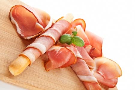 Delicious prosciutto with grissini breadstick on wooden kitchen board. Culinary traditional italian ham background. photo
