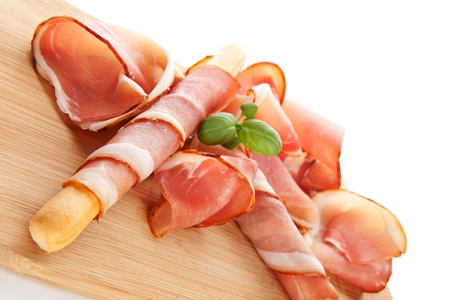 Delicious prosciutto with grissini breadstick on wooden kitchen board. Culinary traditional italian ham background. photo