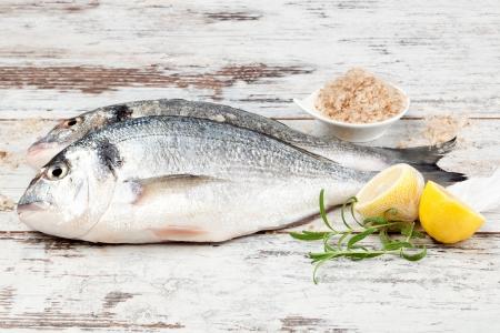 Deux poisson cru doré brème de mer la tête sur fond blanc texturé bois avec des ingrédients culinaires, les herbes fraîches, sel de mer et de citron. Notion de fruits de mer Méditerranée.