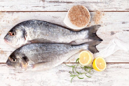 Two fresh sea bream on white wooden textured background with fresh rosemary and lemon. Culinary mediterranean seafood. photo