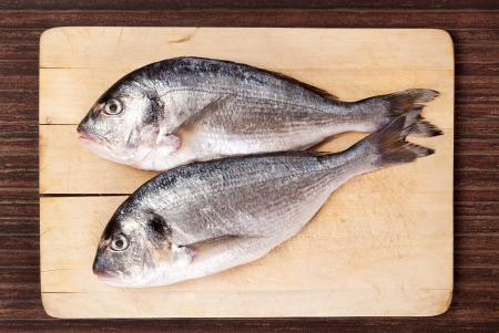 Two fresh sea bream fish on used wooden cutting board on brown background. Culinary seafood eating in natural brown. photo