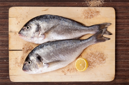 gilt head: Two fresh gilt head fish with lemon and salt crystals on wooden kitchen board on brown background. Culinary mediterranean seafood concept in natural brown. Stock Photo