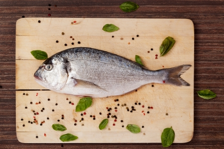 Sea bream on wooden chopping board with colorful peppercorns and basil leaves on brown background. Culinary seafood concept in natural brown.