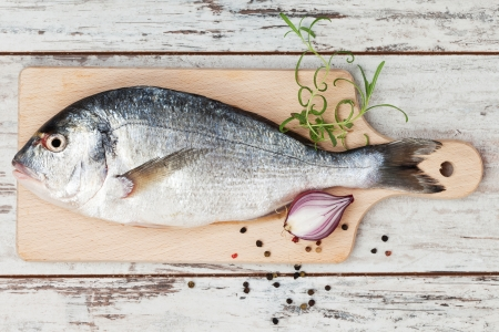 Delicious fresh sea bream fish on wooden kitchen board with onion, rosemary and colorful peppercorns on white textured wooden background  Culinary healthy cooking  photo