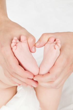 Female caucasian hands holing little baby feet on white background  Security, safety, protection parenting mother and baby concept Stock Photo - 15841954