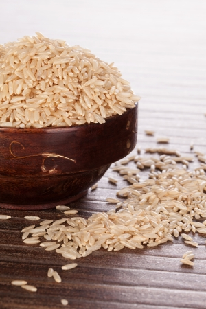 Brown rice in brown wooden round oriental bowl on brown background  Asian rice eating concept