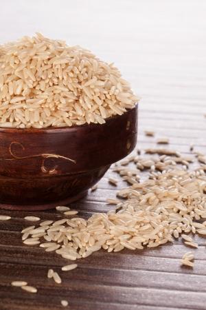 Brunt ris i brunt trä runda orientalisk skål på brun bakgrund Asiatiska ris att äta koncept