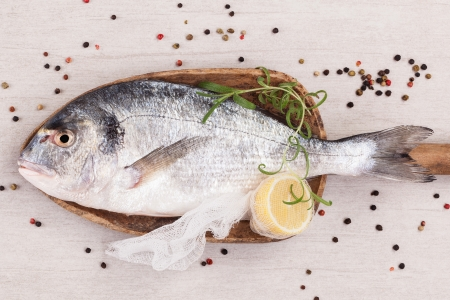 Delicious seafood background  Fresh raw gilt heat on wooden plate with fresh herbs and colorful peppercorns  Culinary fish eating Stock Photo - 16612905