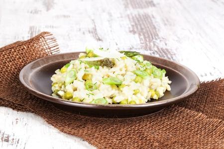 asperges: Heerlijke risotto op bruin plaat op geweven witte houten achtergrond Culinair vegetarisch eten Stockfoto