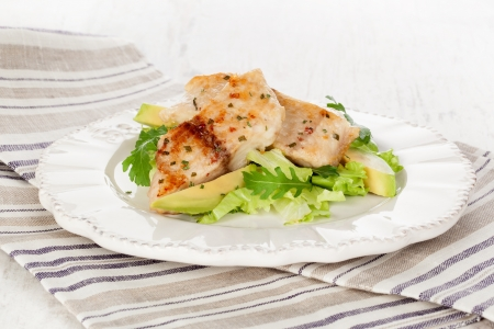 cod fish: Healthy eating  Grilled fish fillet with fresh rocket salad, lettuce and avocado on white plate on white wooden textured background  Stock Photo