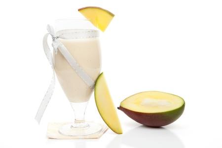 Fresh tropical mango fruit shake with ripe mango fruit isolated on white background. Refreshing healthy summer drink. photo