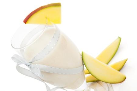 Mango shake with fresh mango fruit isolated on white. Healthy refreshing summer drink. photo