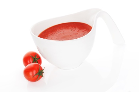 Delicious tomato soup with fresh tomatoes isolated on white background  Culinary healthy soup eating  photo
