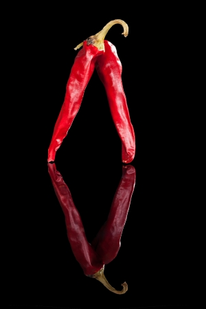 Two red chili pepper isolated on black background  Culinary hot cooking ingredient  photo