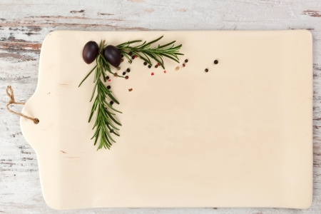 Empty ceramic kitchen board with rosemary and peppercorns in the corner on white wooden textured background as your copy space, top view  Culinary gastronomy background  photo