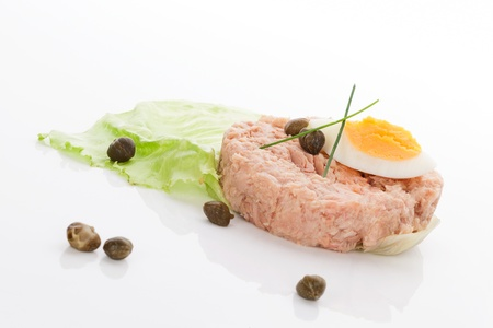 Culinary tuna background  Canned tuna with lettuce, egg and capers isolated on white background  Seafood eating  photo