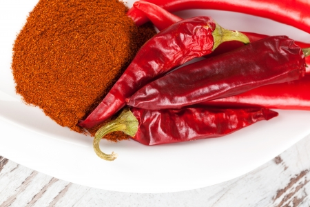 Fresh, dry chili peppers and paprika powder spice on white plate on white wooden background  Culinary cooking spices   photo