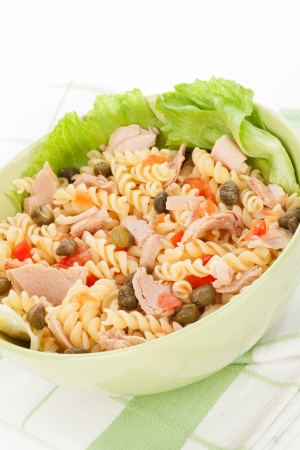 Pasta with tuna, capers, lettuce and vegetable in green bowl on white background  Culinary healthy eating   photo