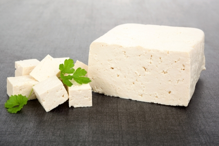 Luxurious tofu background  Tofu piece, cubes and fresh parsley isolated on dark background  Culinary vegan and vegetarian eating