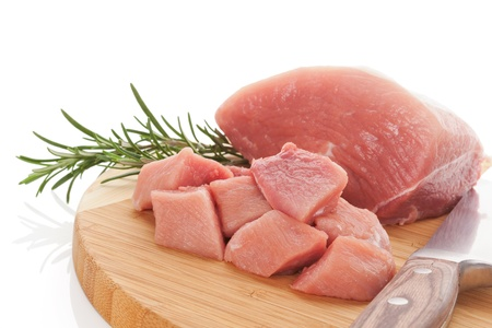 barbecue pork barbecue: Raw pork piece and cubes on round wooden cutting board with fresh rosemary herb isolated on white background  Culinary meat eating concept