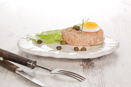 Canned tuna with lettuce, capers and egg on vintage plate  and cutlery on white wooden textured background  Culinary seafood eating, french bright country style  photo