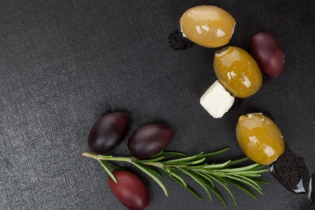 Green and black olives with fresh rosemary twig isolated on dark black and grey background, top view  Culinary mediterranean eating with copy space  photo