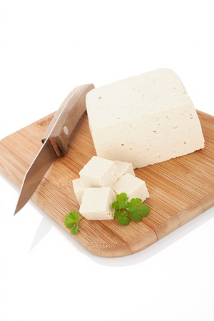 Tofu on wooden kitchen board with kitchen knife and fresh parsley  Culinary vegan and vegetarian eating  photo