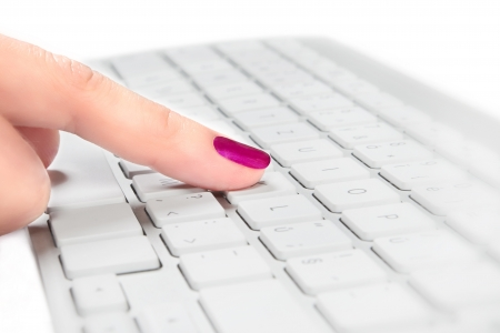Female finger with red fingernail touching silver and white keyboard, selective focus  Help desk concept  photo