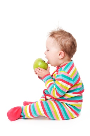 10 month: 10 month old baby sitting and eating green apple isolated on white background Stock Photo