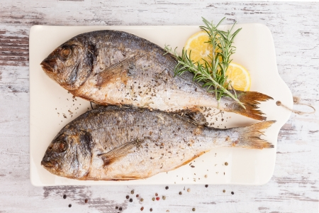 Delicious grilled sea bream fish on kitchen board with rosemary, lemon and colorful peppercorns on white textured wooden background. Culinary healthy cooking. photo