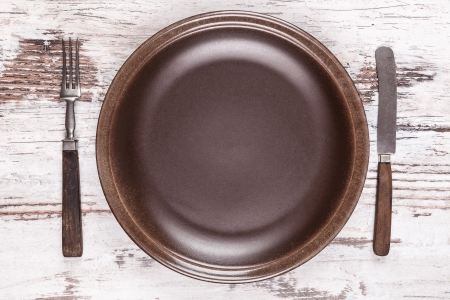 Brown empty plate and wooden vintage cutlery on white wooden background top view  Gastronomy background with copy space, rustic styles  photo