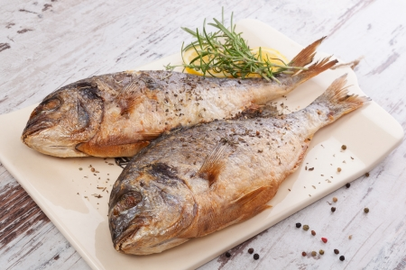 Two grilled fish with lemon and rosemary on ceramic kitchen board on white wooden background  Culinary mediterranean fish eating   photo