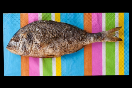gilt head: Grilles gilt head bream fish on colorful napkin, top view  Culinary summer seafood concept  Healthy eating