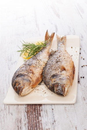Two grilled sea bream fish on ceramic vintage cutting board on white wooden background with lemon and rosemary  Delicious healthy mediterranean seafood eating  photo