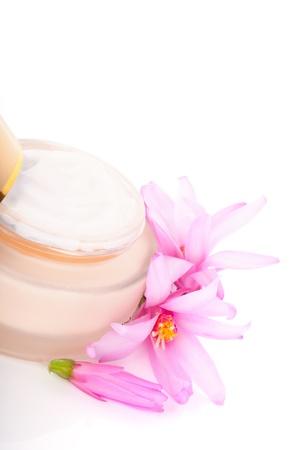 moisturiser: Golden anti aging cream moisturiser with pink flower isolated on white background  Luxurious cosmetic background