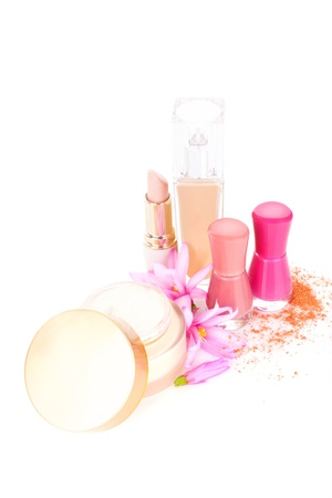 Cosmetic background in beige and pink  Anti aging lotion, beige lipstick, foundation, nail polish, face powder and pink blossom isolated on white background  Luxurious feminine fashion concept  Stock Photo - 18925136