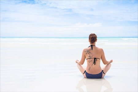 Rear view of beautiful young woman with tattoo doing yoga on beach. Wellbeing concept. Stock Photo