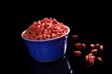 Dried goji berries in blue bowl isolated on black background photo