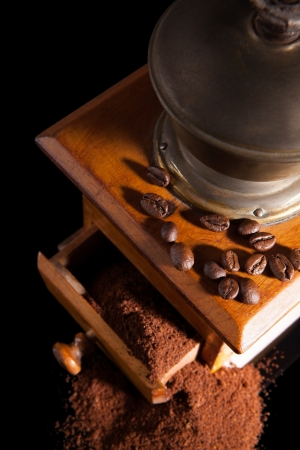 Old vintage coffee mill with ground coffee isolated on black background photo