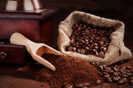 Ground coffee, coffee beans, coffee grinder, wooden spoon with coffee and bag with coffee beans on dark wooden background Stock fotó