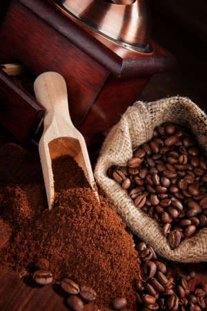 Coffee beans, ground coffee, vintage coffee mill and sack with coffee beans on brown wooden background photo