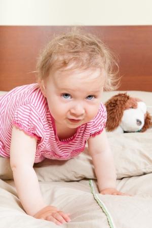 12 month old: Adorabile 12 mesi di et� bambina con grandi occhi blu sul letto con il suo giocattolo preferito guardando in camera.