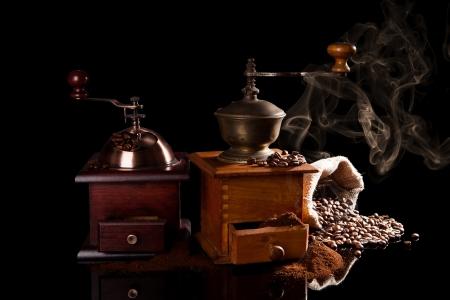 Old Vintage Holz Kaffeemühlen mit gemahlenem Kaffee, Sack mit Kaffeebohnen und der Duft von frischem Kaffee auf schwarzem Hintergrund isoliert Standard-Bild