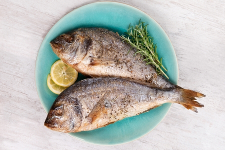 Two grilled barbeque sea bream on plate with fresh rosemary herbs and lemon on white wooden background Culinary mediterranean seafood eating Stock Photo