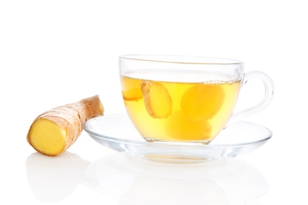 raw tea: Delicious ginger tea in transparent tea cup with saucer and ginger root and ginger slices isolated on white background  Alternative medicine concept