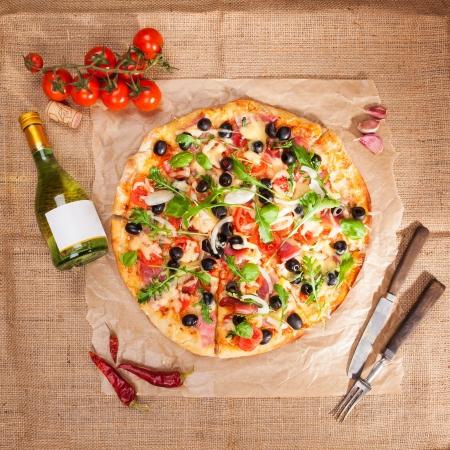 Heerlijke lekkere pizza, verse tomaten, knoflook, fles witte wijn en houten bestek op bruine achtergrond, bovenaanzicht Rustieke stijl Italiaanse eten concpept