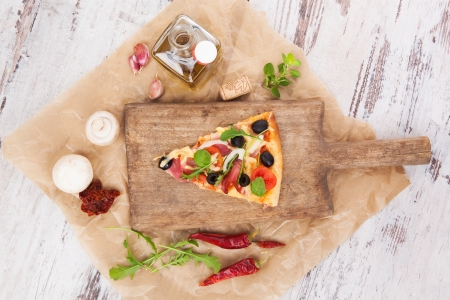 Culinary pizza cooking  Pizza piece on wooden kitchen board, with various ingredients and toppings  Fresh herbs, olive oil, garlic, edible mushrooms, dried tomatoes and chili pepper  Pizza eating  photo