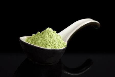 Green wheatgrass powder on ceramic spoon isolated on black background. Alternative medicine concept. Dietary supplement photo