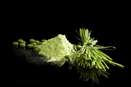 detoxification: Healthy green supplements. Spirulina, wheatgrass, young barely, chlorella sa ground, green pills and fresh wheatgrass isolated on black background. Healthy lifestyle concept.
